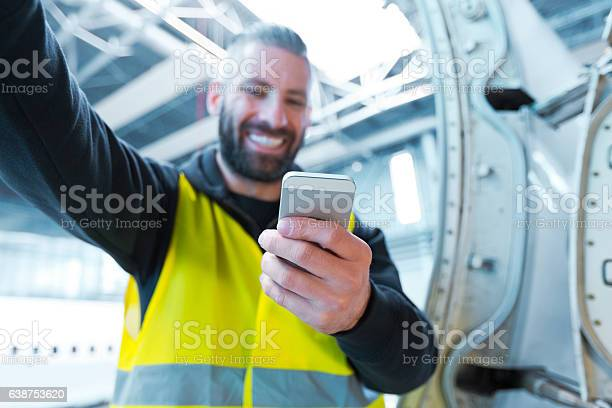 Aircraft Engineer Using A Smart Phone In A Hangar Stock Photo - Download Image Now