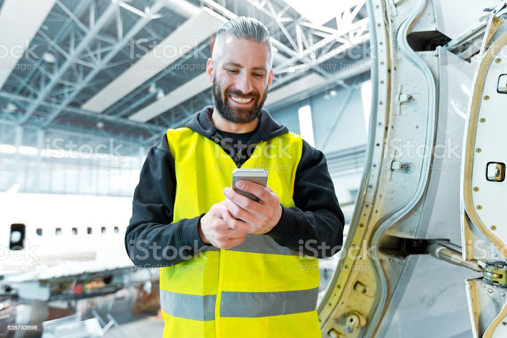 Aircraft engineer using a smart phone in a hangar Aircraft engineer using a smart phone in a hangar.  Adult Stock Photo