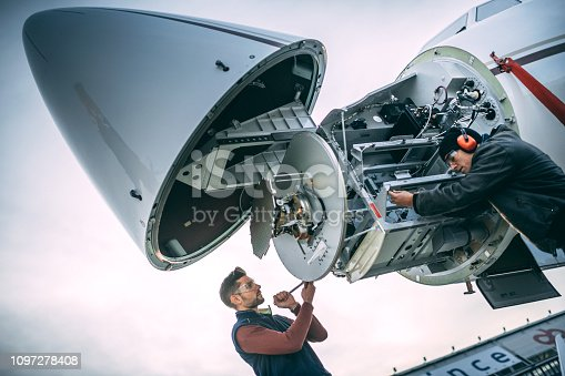 Aircraft engineers working on a radar array under the nose cone of a private airplane parked on an airport field.