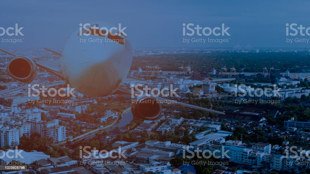 Aircraft fly over cityscape and modern buildings during the night. stock photo