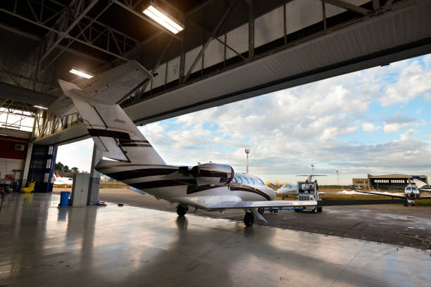 Aircraft in the hangar Private jet aircraft in the hangar open for regular maintenance service. airplane hangar stock pictures, royalty-free photos & images