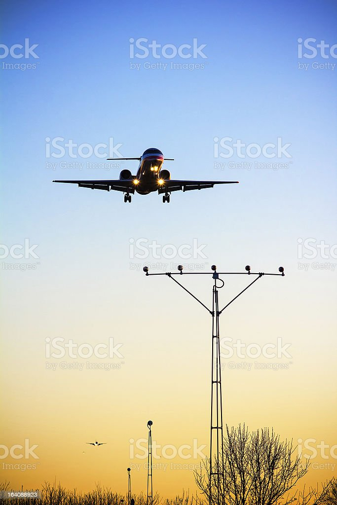 Aircraft is landing at sunset royalty-free stock photo