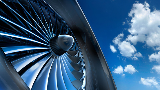 Close-up of aircraft jet engine turbine against a blue sky with white clouds