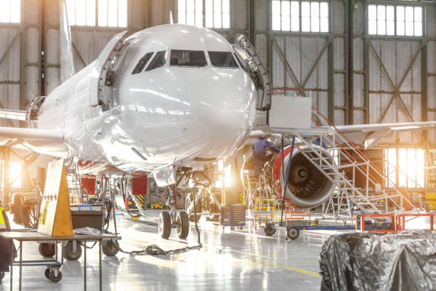 Aircraft jet on maintenance of engine and fuselage check repair in airport hangar. Aircraft jet on maintenance of engine and fuselage check repair in airport hangar airplane hangar stock pictures, royalty-free photos & images