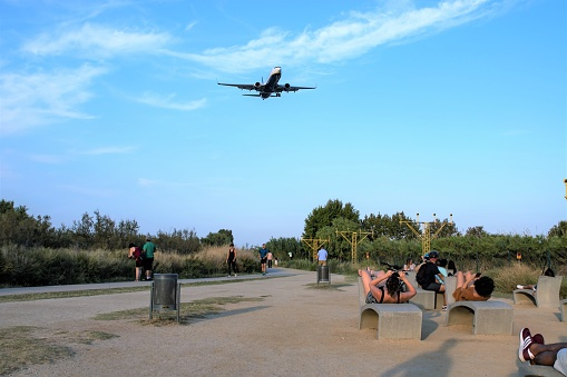 Aircraft landing in El Prat Barcelona airport overflying a group of people