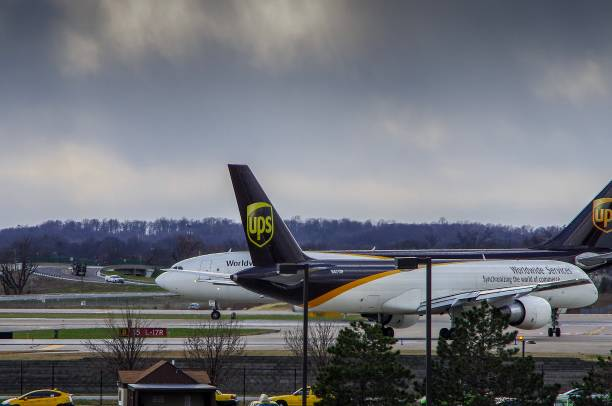 Aircraft lining up at end of runway to depart Louisville, KY—Mar 6, 2018; United Parcel Service cargo aircraft pass each other while taxing prior to taking off.  UPS is a major logistics and air freight company with a avaiation hub and corporate headquarters in Louisville, Kentucky. depart stock pictures, royalty-free photos & images