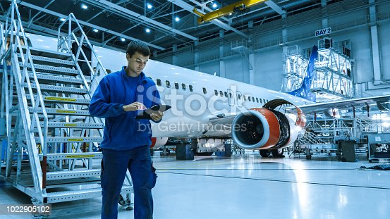 Aircraft maintenance mechanic in blue uniform is going down the stairs while using tablet in a hangar.