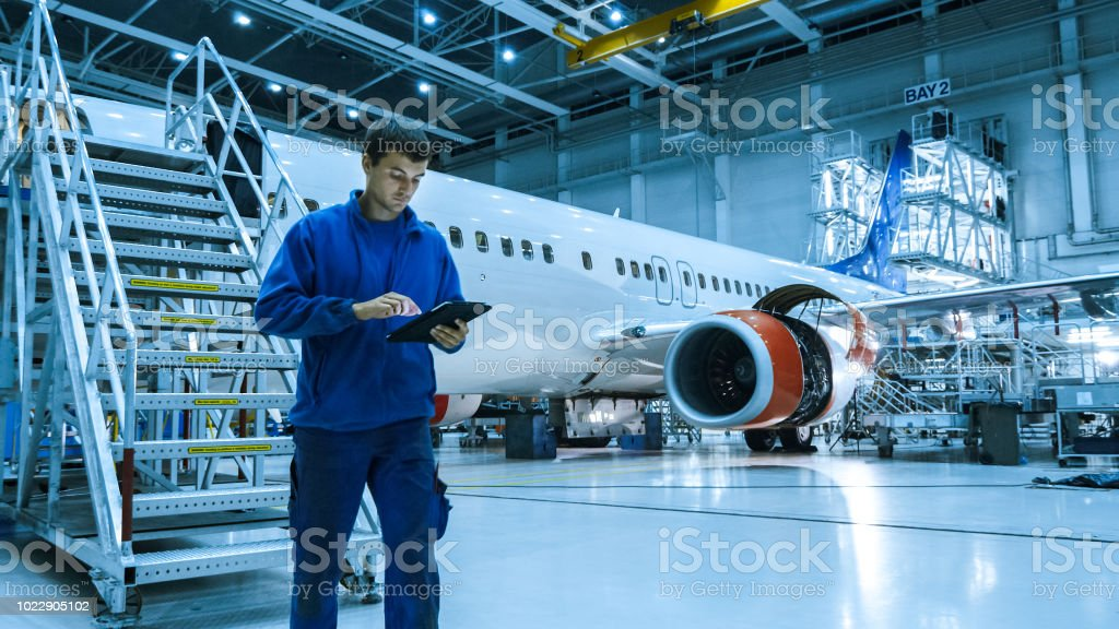 Aircraft maintenance mechanic in blue uniform is going down the stairs while using tablet in a hangar. stock photo