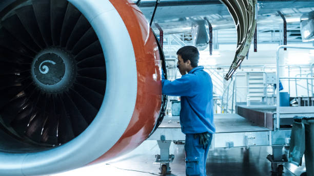 Aircraft maintenance mechanic inspects and tunes plane engine in a hangar. stock photo