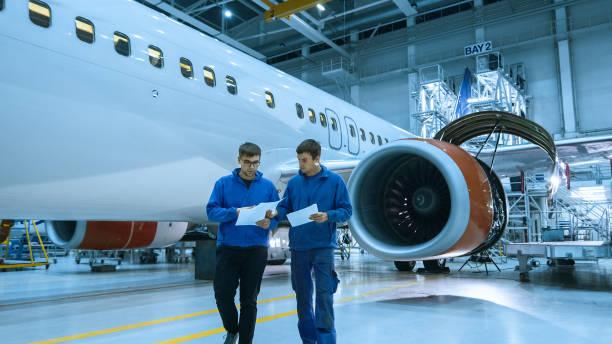 航空機整備士は、格納庫内の飛行機のキャビンの前にタブレットを使用します。 - 航空整備士 ストックフォトと画像