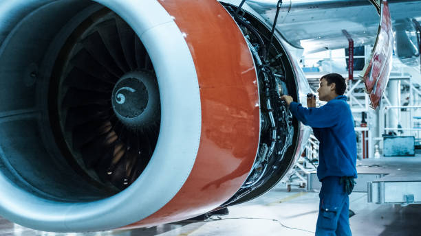 Aircraft maintenance mechanic with a flash light inspects plane engine in a hangar. stock photo