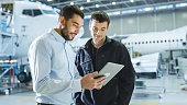 istock Aircraft Maintenance Worker and Engineer having Conversation. Holding Tablet. 1022905428