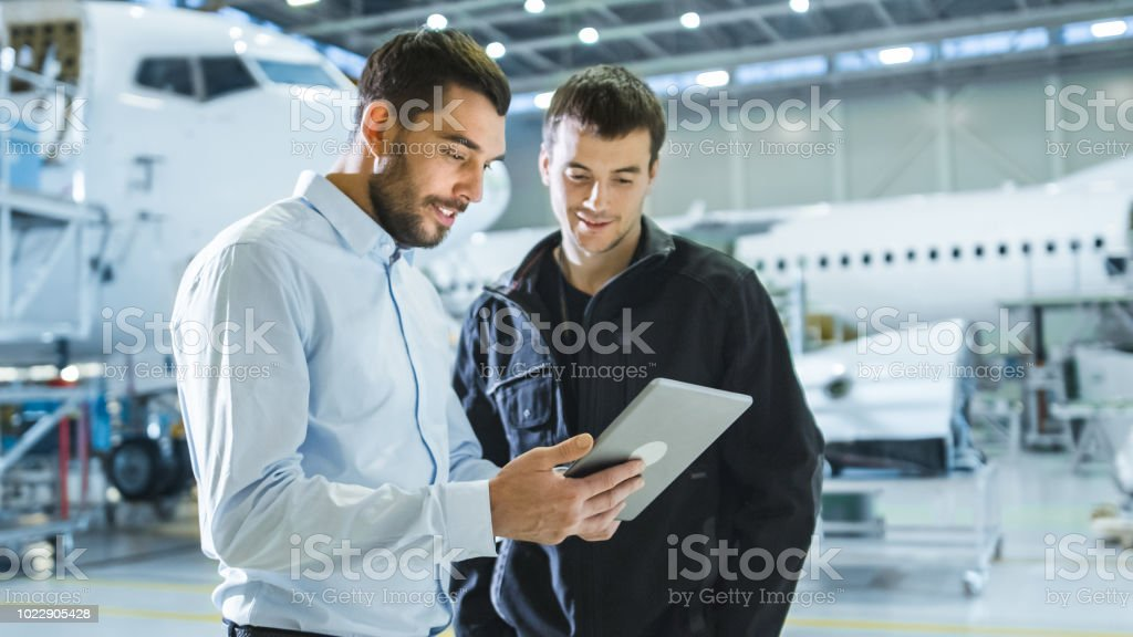 Aircraft Maintenance Worker and Engineer having Conversation. Holding Tablet. stock photo