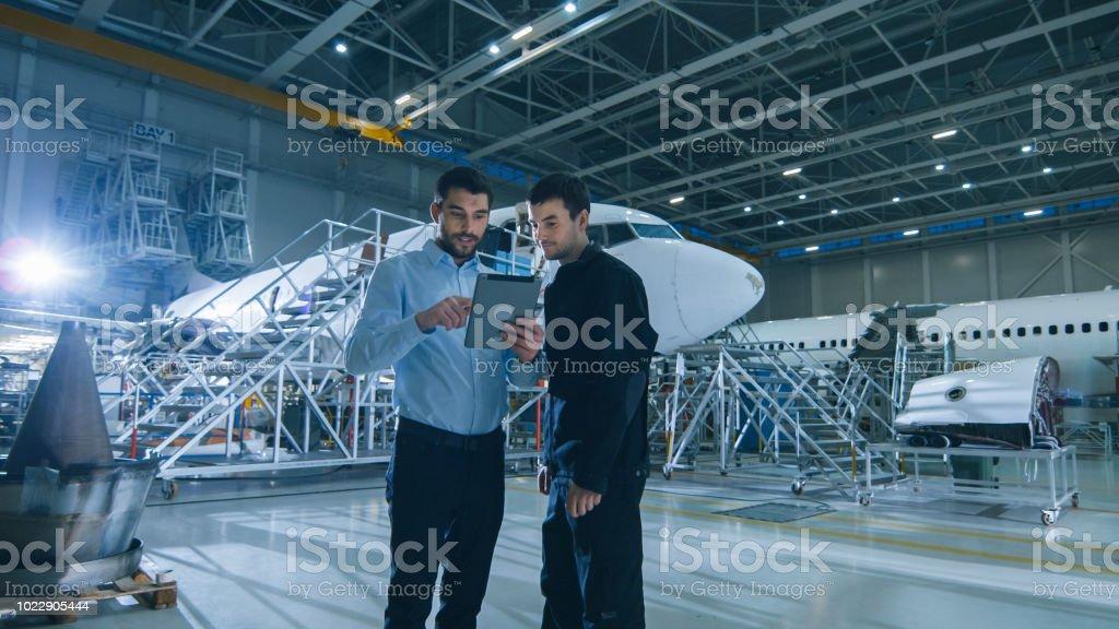 Aircraft Maintenance Worker and Engineer having Conversation. Holding...