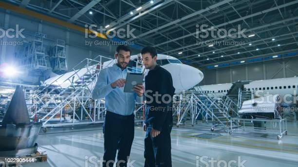 Aircraft maintenance worker and engineer having conversation holding picture id1022905444?b=1&k=6&m=1022905444&s=612x612&h=clhzhnenp0flkvzvd2r5q95yhjipgnmgopfs7n70wqy=