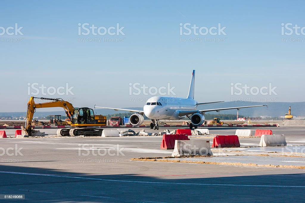 Aircraft maneuvering between excavators and bulldozers stock photo