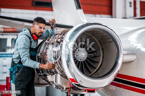 Aircraft mechanic inspecting and checking the technology of a jet engine in the hangar at the airport.