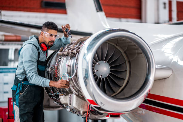 Aircraft Mechanic checking jet engine of the airplane stock photo