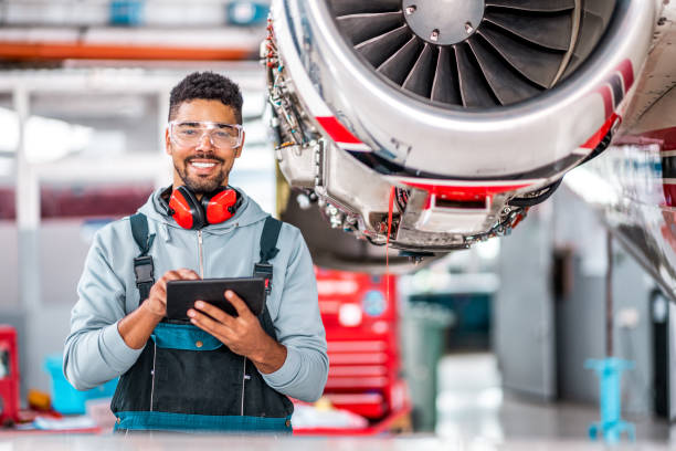 Aircraft mechanic holding a tablet in the hangar stock photo