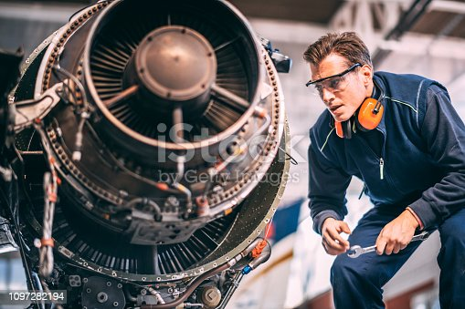 Aircraft engineer in the hangar repairing and maintaining an airplane jet engine.