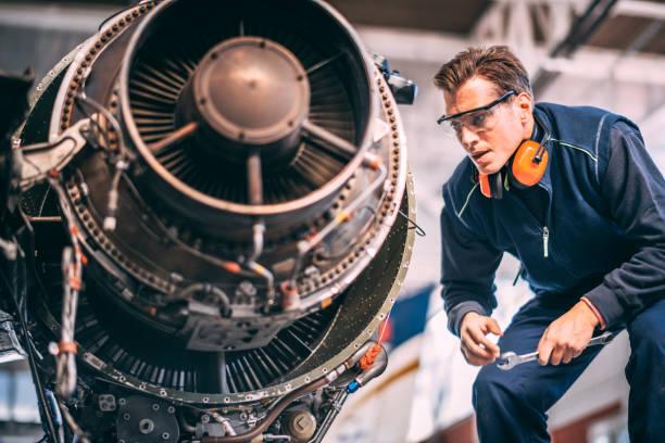 Fluggerätmechaniker in einem Hangar halten einen Schraubenschlüssel und Reparatur und Wartung ein kleines Flugzeug Jet-engine – Foto