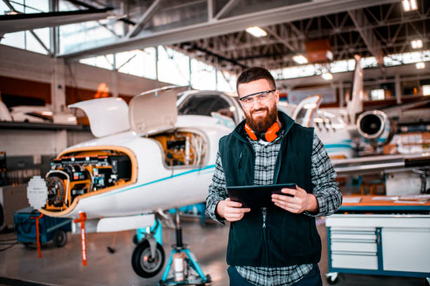 Flugzeugmechaniker in einem Hangar lächelnd und mit Blick auf eine Kamera, während sie ein Tablet halten und ein Flugzeug reparieren und warten – Foto