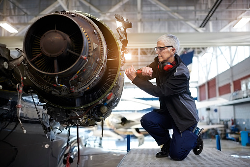 Senior female engineer in the hangar repairing and maintaining airplane jet engine.
