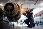 Senior female engineer in the hangar repairing and maintaining airplane jet engine.
