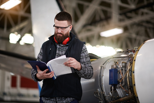 Male aircraft engineer in the hangar reading instruction manuals before repairing and maintaining private jet airplane.