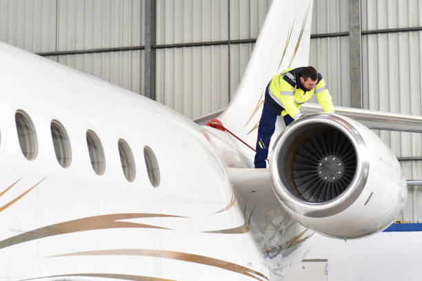 Aircraft mechanic inspects and checks the technology of a jet in a hangar at the airport stock photo