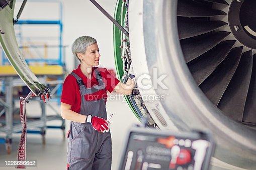 Aircraft mechanic is working in an airplane hangar