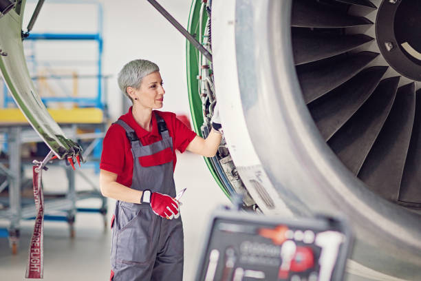 Aircraft mechanic is working in an airplane hangar stock photo