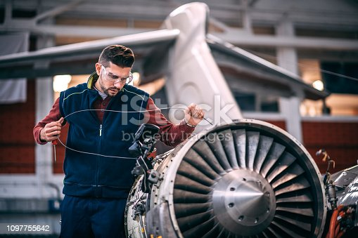 Aircraft engineer in the hangar holding a camera probe while repairing and maintaining airplane jet engine.