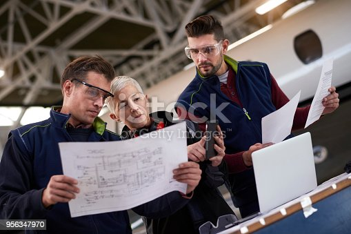 Team of three aircraft engineers in the hangar reading manuals before repairing and maintaining jet airplane.