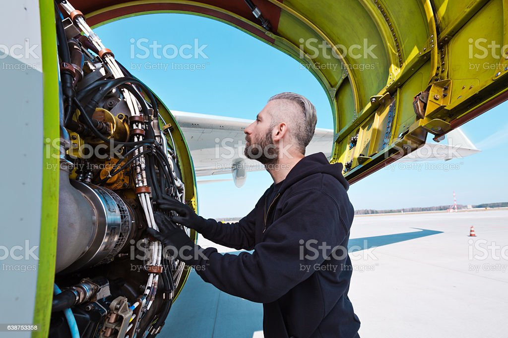 Aircraft mechnic examining aircraft engine Aircraft mechanic standing outdoor in front of airplane engine. Adult Stock Photo
