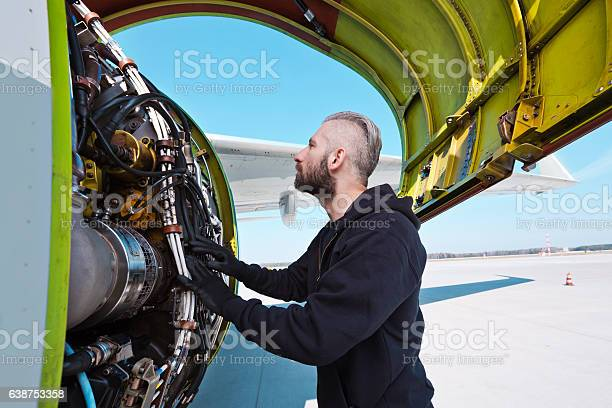 Aircraft Mechnic Examining Aircraft Engine Stock Photo - Download Image Now