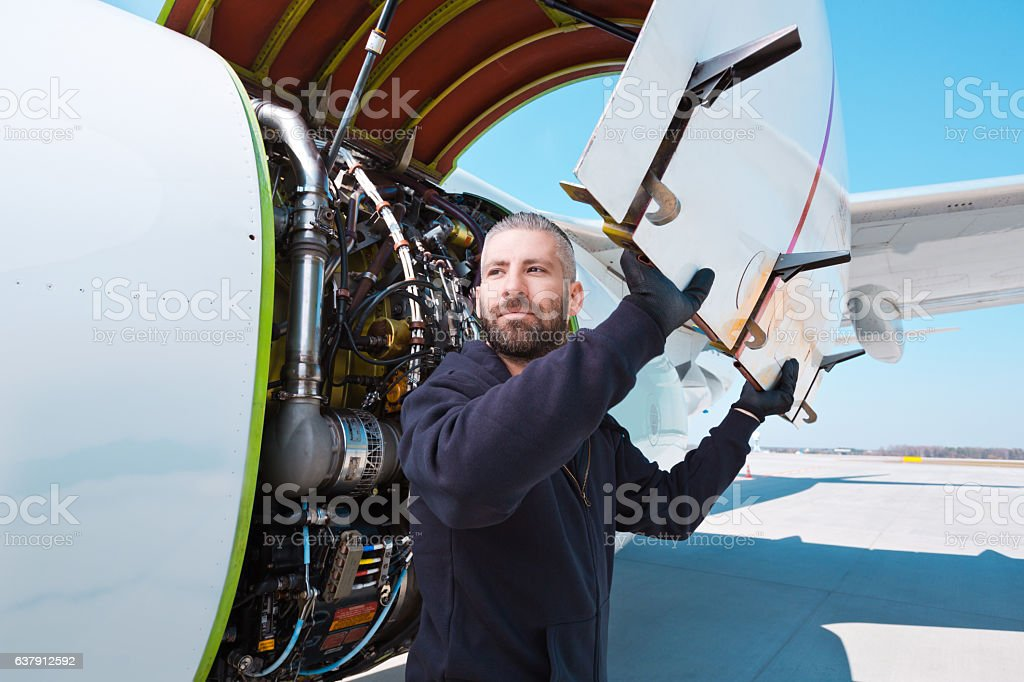 Aircraft mechnic in front of aircraft engine Aircraft mechanic standing outdoor in front of airplane engine. Adult Stock Photo