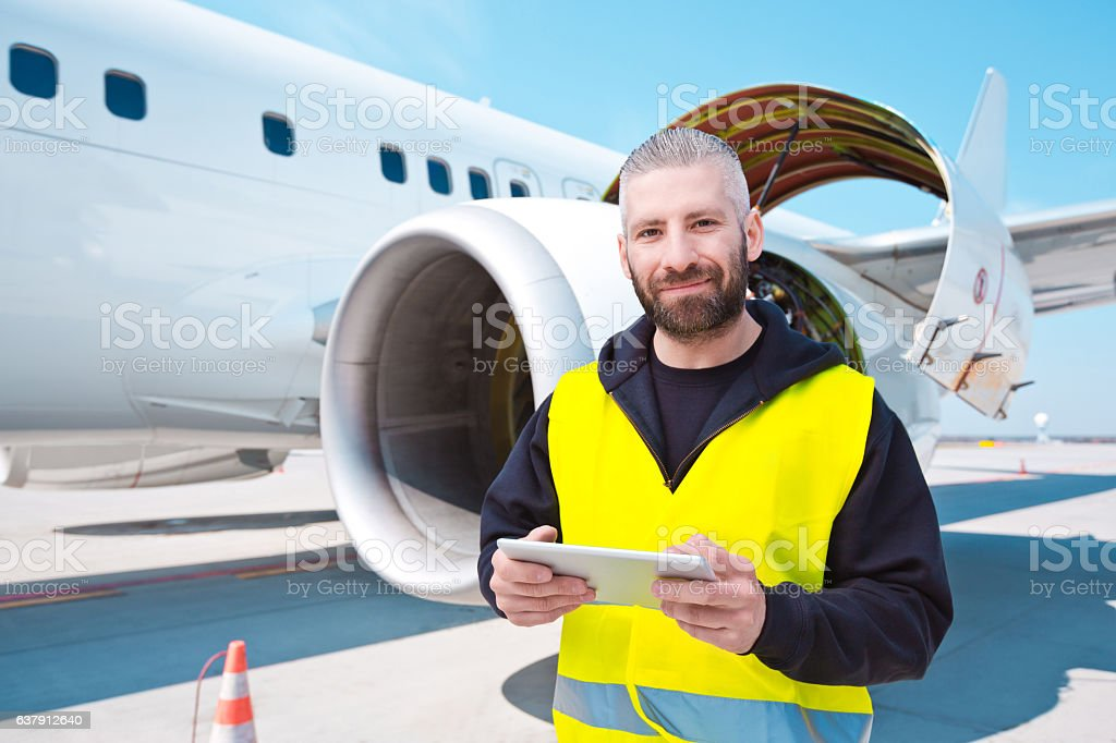 Aircraft mechnic in front of aircraft engine Aircraft mechanic standing outdoor in front of airplane engine, holding a digital tablet in hands, smiling at the camera. Adult Stock Photo