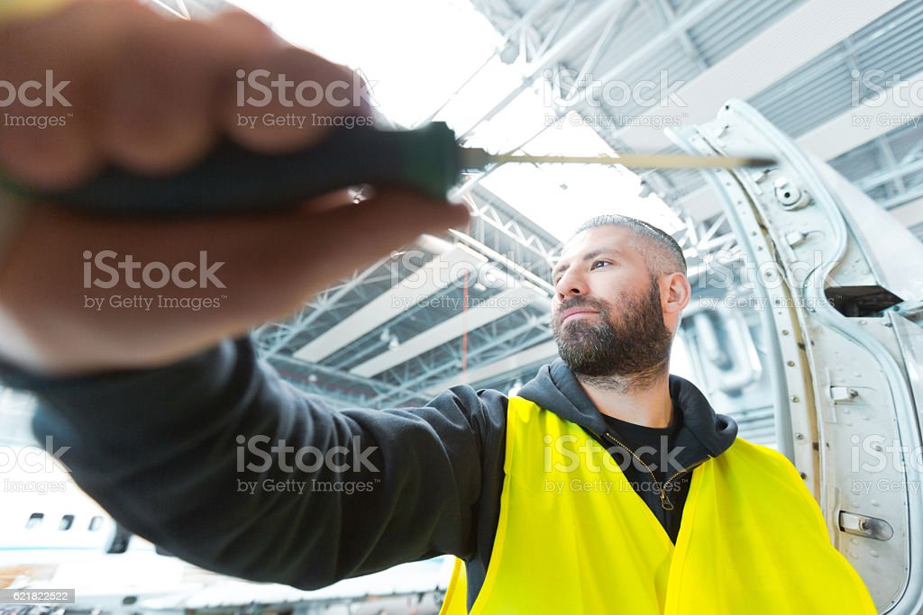 Aircraft mechnic repairing airplane in a hangar Aircraft mechnic holding screwdriver and repairing airplane in a hangar. Adult Stock Photo