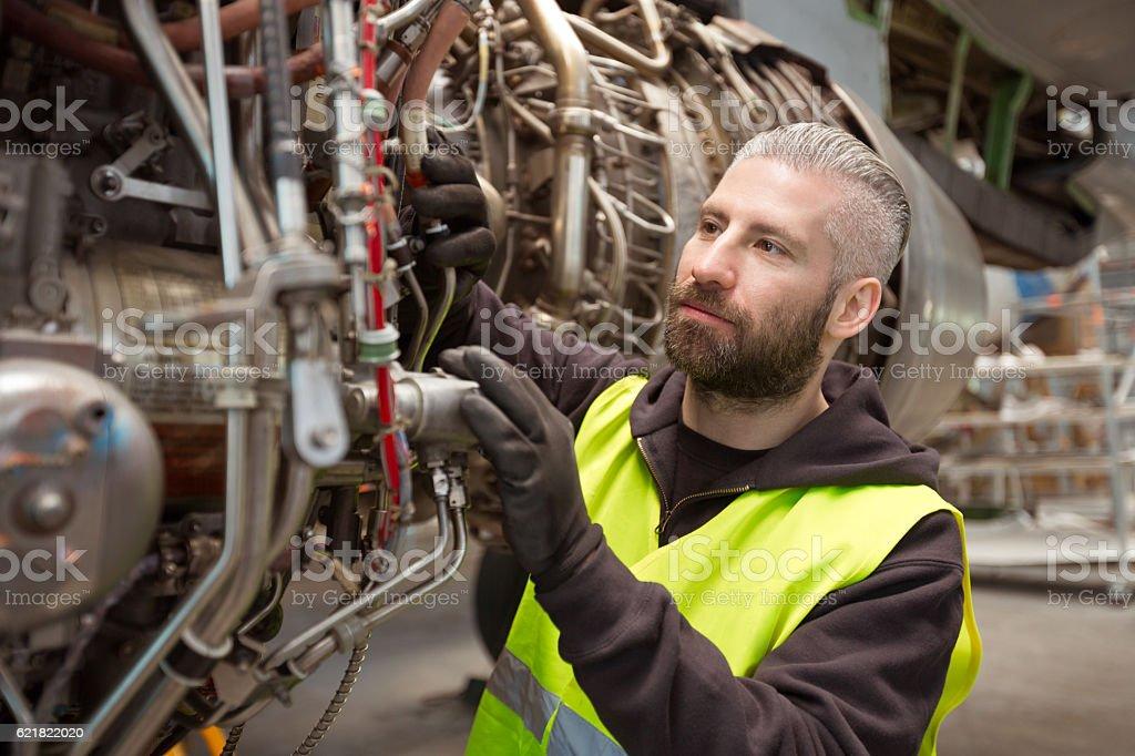 Aircraft mechnic repairing jet engine Aircraft mechnic repairing jet engine in a hangar. Adult Stock Photo