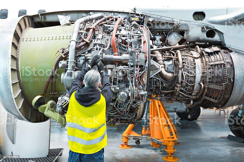 Aircraft mechnic repairing jet engine Back view of aircraft mechnic repairing jet engine in a hangar. Adult Stock Photo