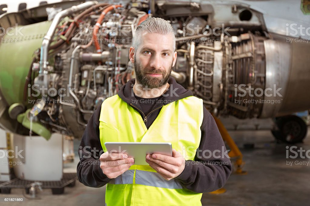 Aircraft mechnic using a digital tablet in a hangar Aircraft mechanic using a digital tablet in a hangar, standing in front of jet engine and looking at camera. Adult Stock Photo