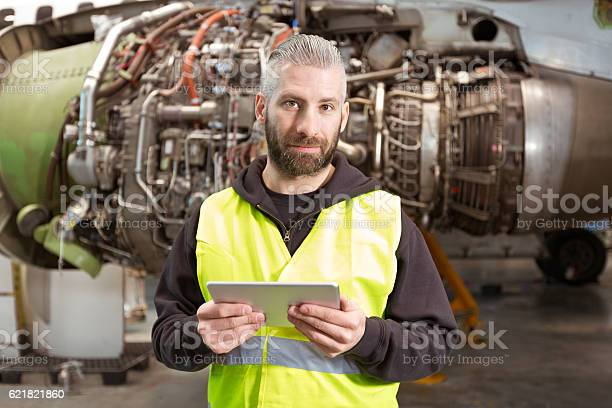 Aircraft Mechnic Using A Digital Tablet In A Hangar Stock Photo - Download Image Now