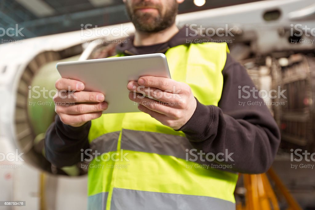Aircraft mechnic using a digital tablet in a hangar Aircraft mechanic using a digital tablet in a hangar, standing in front of jet engine, close up of hands. Adult Stock Photo