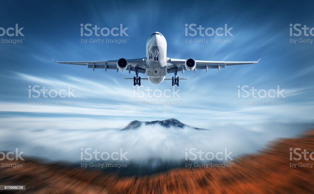 Aircraft mith motion blur effect is flying over low clouds. Landscape with passenger airplane, blurred clouds, mountains, blue sky. Passenger airplane. Business travel. Commercial plane. Concept stock photo