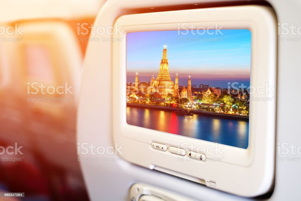 Aircraft monitor in passenger seat on Wat Arun night view Temple in bangkok, Thailand background stock photo