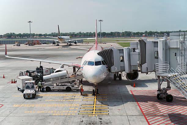 Aircraft preparing to depart Changi Airport, Singapore - May 17, 2016: Thai Air Asia's aircraft preparing to depart from Changi Airport depart stock pictures, royalty-free photos & images