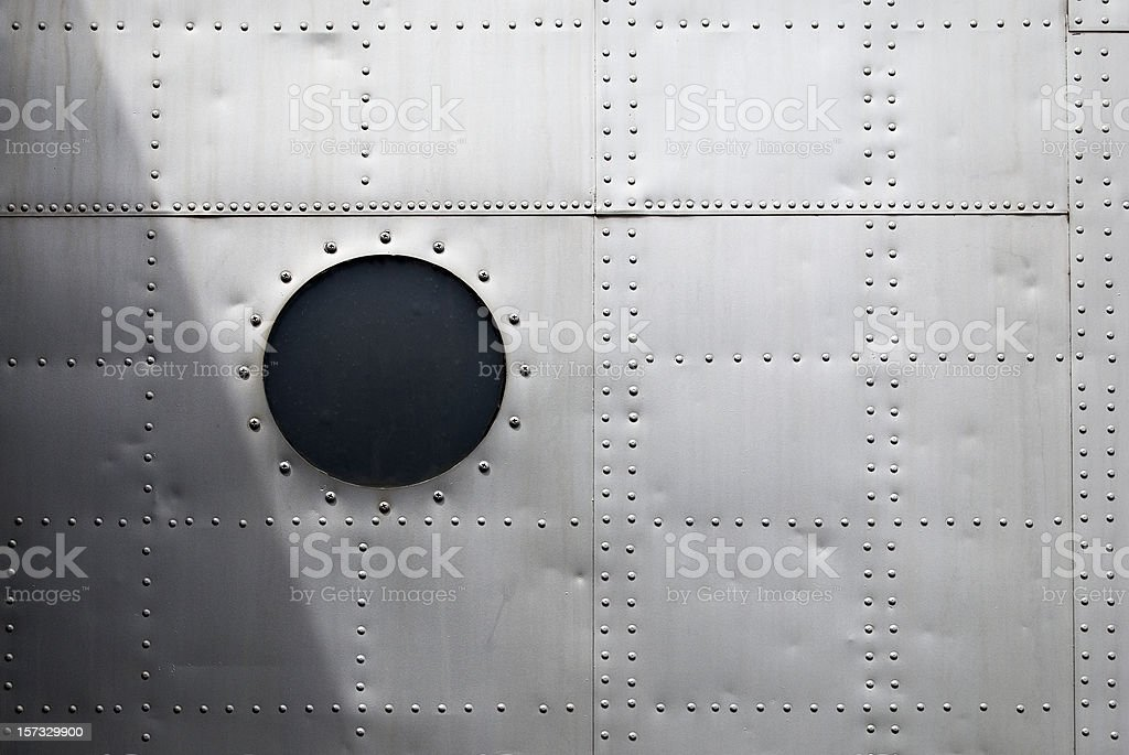Aircraft siding with circular window and rows of rivets stock photo