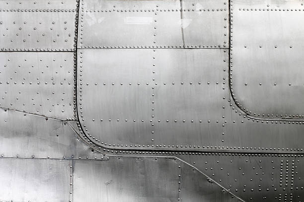 Aircraft siding with rivets Aluminum fuselage and rivets in old airplane. sheet metal stock pictures, royalty-free photos & images