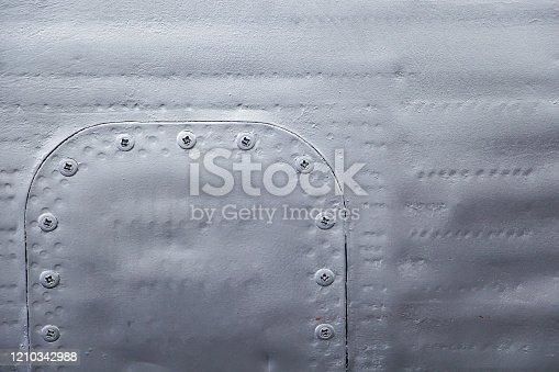 487808089 istock photo Aircraft skin close up. Rivets on gray metal. 1210342988